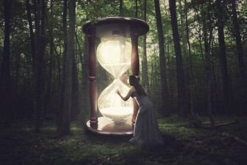 A woman finds a huge hourglass in the forest.